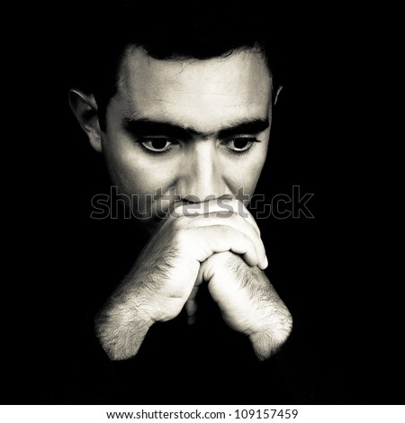 Dramatic black and white face of a worried young man  emerging from a black background - stock photo