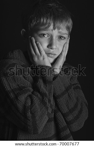 dramatic black and white image of a young blonde boy who is scared