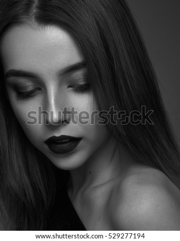 Dramatic black and white portrait of a beautiful girl on a dark background in the studio
