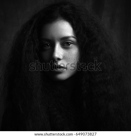 Dramatic black and white portrait of a beautiful lonely girl with freckles isolated on a dark