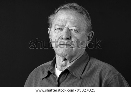 Dramatic black and white portrait of a senior man looking very serious, sad or depressed looking at camera,great facial details, shot in studio over black.