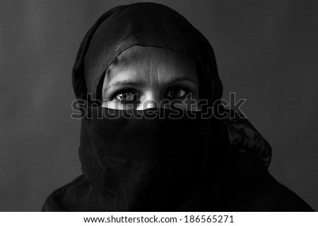 Dramatic black and white portrait of a veiled middle-aged muslim woman with strong gaze            - stock photo