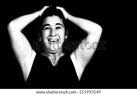 Dramatic black and white portrait of a very angry and depressed woman screaming isolated on black with space for text - stock photo