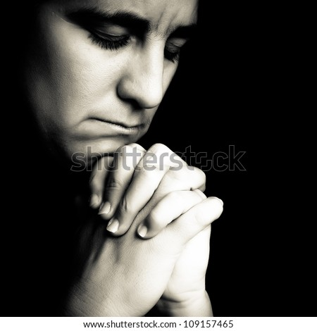 Dramatic black and white portrait of a woman  praying or thinking emerging from a black background - stock photo