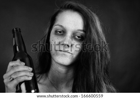 Dramatic black and white portrait of a young woman addict with beer, junkie, alcohol or drug addiction. - stock photo