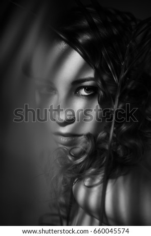 Dramatic black and white portrait of girl with shadows on her face
