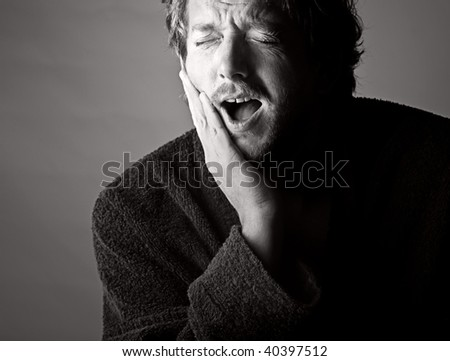 Dramatic Black and White Shot of a Man in Pain holding his Jaw. Toothache! - stock photo