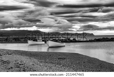 Dramatic Black and White Two Boats at Sunset Rocky Harbor Gros Morne Park Newfoundland - stock photo