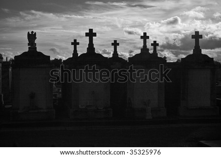 Dramatic black & white silhouette of New Orleans above ground cemetery - stock photo