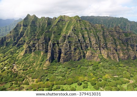 Dramatic cliffs of Kualoa Ranch - view from helicopter, Oahu, Hawaii - stock photo