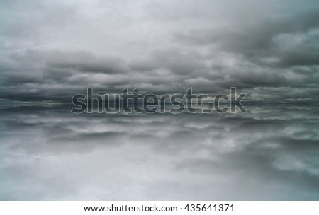 Dramatic cloud reflections in a dead calm lake background texture.