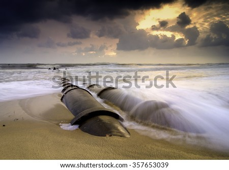 dramatic clouds and blurred image during sunrise sunset at the beach. stunning wave and concrete structure and beautiful sand - stock photo
