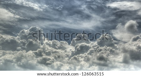 Dramatic clouds forming mountain in sky - stock photo
