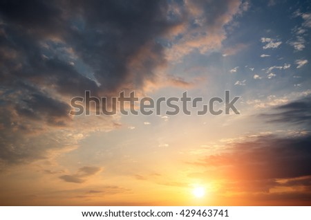 Dramatic clouds in the sky and the sun at sunset