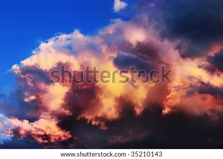 Dramatic clouds on the blue sky on the sunset - stock photo