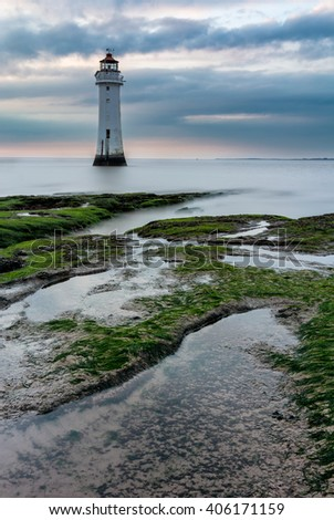 Dramatic clouds with old British lighthouse and interesting rocks in foreground at New Brighton Beach in Merseyside, UK.