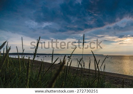 Dramatic cloudscape sunset at sea gulf with tall grass on beach - stock photo