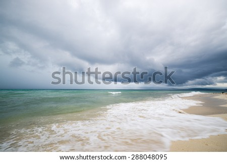 Dramatic cloudscape with heavy rain and tropical storm at the horizon on the coastline of Tanjung Karang, Central Sulawesi, Indonesia. Wide angle shot with waves in the foreground, blurred motion. - stock photo