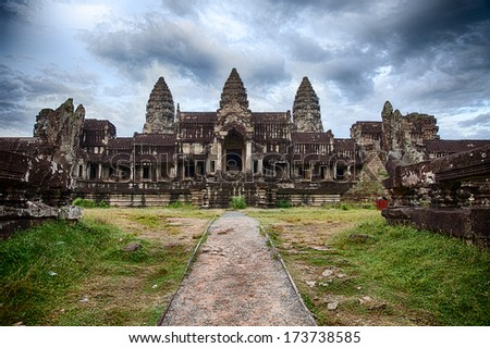 Dramatic cloudy skies show over Angkor Wat as seen from path at the rear entrance to the three-tiered pyramid temple. The five towers, or quincunx, of the historic site are visible. - stock photo