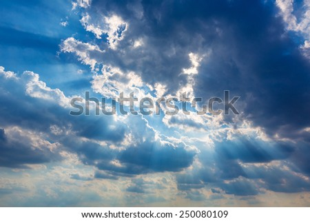 Dramatic cloudy sky clouds with real sun beams background - stock photo