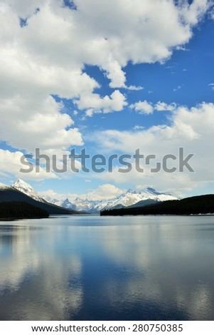 Dramatic Cloudy sky over Canadian Rockies reflected in Maligne Lake