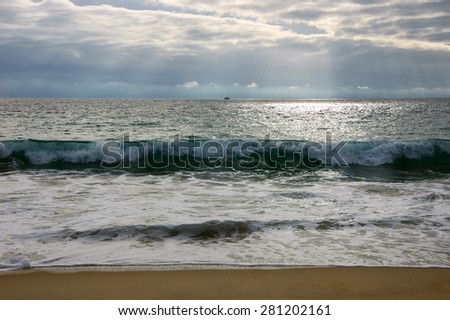 Dramatic cloudy sunset with sunbeams over Atlantic Ocean coast. Fishing ship sailing on horizon under sun rays glowing through the clouds. Nazare, Portugal. - stock photo