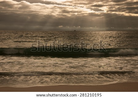 Dramatic cloudy sunset with sunbeams over Atlantic Ocean coast. Fishing ship sailing on horizon under sun rays glowing through the clouds. Nazare, Portugal. Toned photo. - stock photo