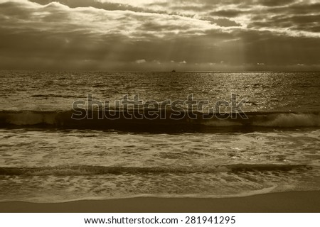 Dramatic cloudy sunset with sunbeams over Atlantic Ocean coast. Fishing ship sailing on horizon under sun rays glowing through the clouds. Nazare, Portugal. Aged photo. Sepia. - stock photo