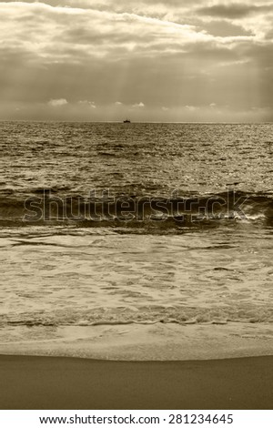 Dramatic cloudy sunset with sunbeams over Atlantic Ocean. Fishing ship (surrounded by flock of seagulls) sailing on horizon in sunrays glowing through the clouds. Nazare, Portugal. Aged photo. Sepia. - stock photo