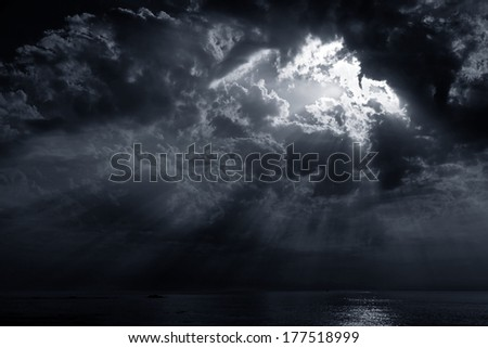 Dramatic cloudy sunset with sunbeams. Portuguese coast. Toned blue. - stock photo
