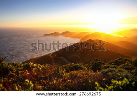 Dramatic coastal sunset with island peninsula and golden light ocean - stock photo