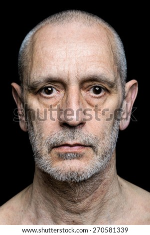 Dramatic color portrait of an adult man with sad expression on black background