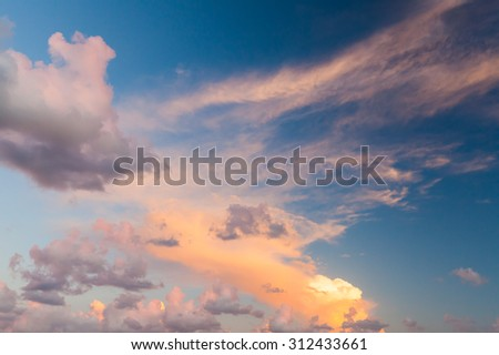 Dramatic colorful cloudscape, summer evening sky background texture with different types of clouds in the sunlight - stock photo