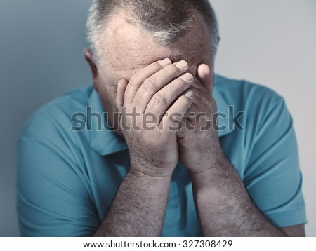 Dramatic cool toned close up portrait of aged man sitting with hands on his face against white wall - depression concept