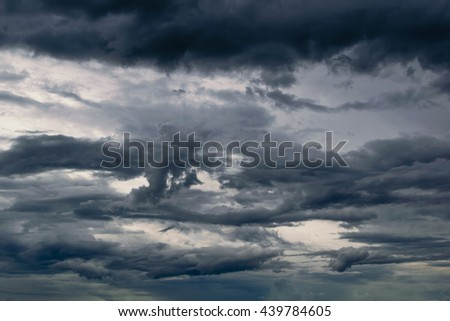 Dramatic dark clouds with thunderstorm in rainy season,Birds  flying back to the nest during rain - stock photo