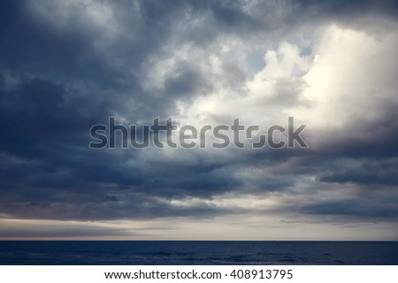Dramatic dark cloudy sky over sea, natural photo background - stock photo