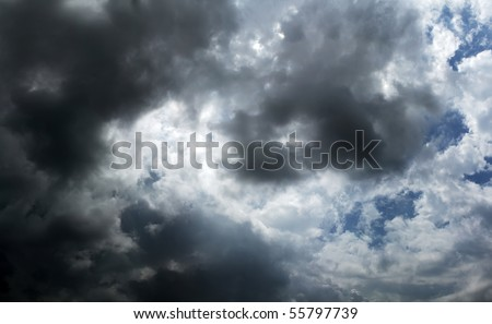 dramatic dark storm clouds passing over head - stock photo