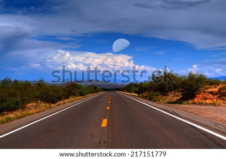Dramatic desert mountain road with moon and storm approaching - stock photo