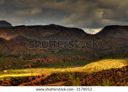 Dramatic desert mountains with a storm approaching and horses in the distant pasture - stock photo