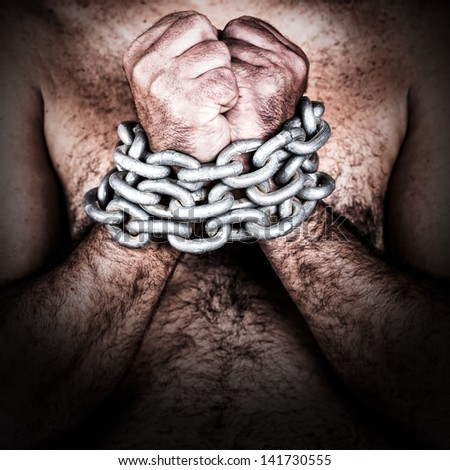 Dramatic detail of the chained hands of an adult shirtless man (with a strong chain and padlock) - stock photo