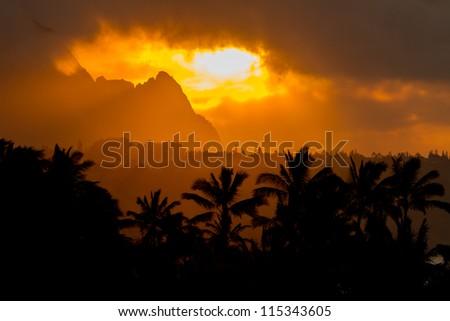 Dramatic evening orange glow near Bali Hai and coconut trees in the foreground. Taken in Kauai - stock photo