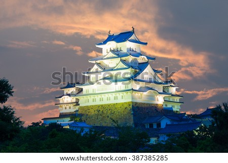Dramatic evening orange sunset sky behind lighted Himeji-jo castle using telephoto lense for magnified close up details in Himeji, Japan after 2015 renovations finished. Horizontal copy space