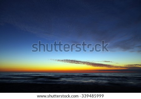 Dramatic evening sky over ocean or sea. Beautiful seascape scene with horizon and sky. Tranquil scene ideal for wallpaper or background. - stock photo