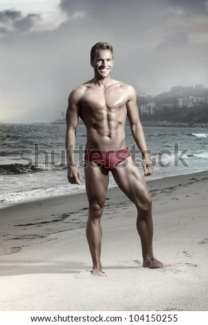 Dramatic fashion portrait of athletic fit male model on beach in bikini swimwear - stock photo