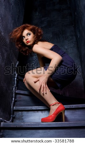 Dramatic full-body portrait of a gorgeous fashion model in spooky surroundings - stock photo
