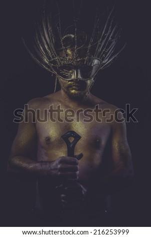 dramatic golden bodypaint, man with gold helmet, ancient warrior deity - stock photo