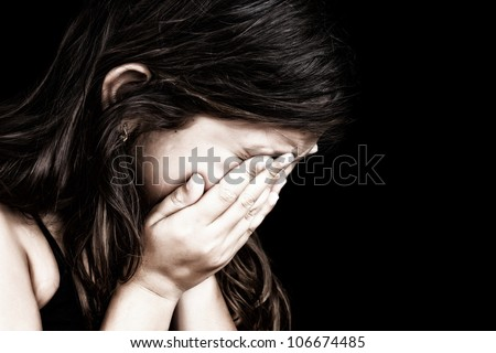 Dramatic grunge portrait of a girl crying with her hands on her face isolated on a black background
