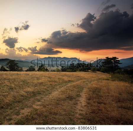 dramatic HDR image with mountain road at dusk time - stock photo