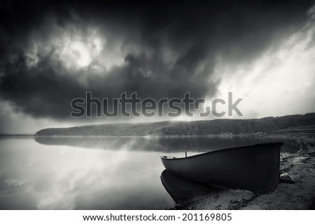 dramatic high contrasted black and white landscape with alone boat near lake  - stock photo