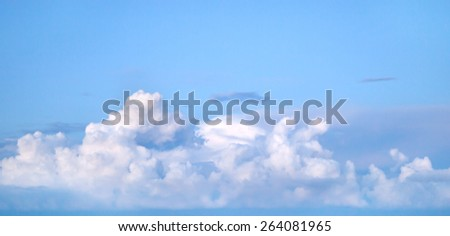 Dramatic huge fluffy clouds on vivid blue sky - stock photo